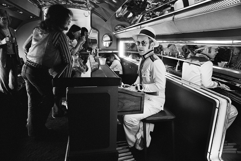Elton John, Playing Piano on Airplane, 1975